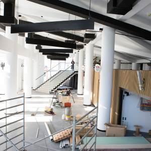 Prace remontowe w holu. Na pierwszym planie widać rusztowanie. Na podłodze znajdują się kartony. Dalej stoi drewniany stół z narzędziami.