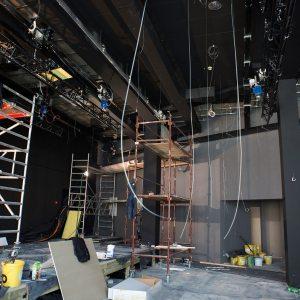 Klubokawiarnia. Prace remontowe na scenie.  Mężczyzna stoi na rusztowaniu, montując reflektor.