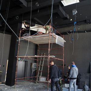 Klubokawiarnia. Dwóch mężczyzn pracuje na rusztowaniu. Obok stoi jeszcze czterech pracowników.