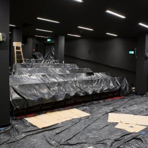 Mała sala kinowa. Widok z rogu sceny. Rzędy foteli i podłoga zabezpieczone zostały czarną folią.