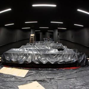 Mała sala kinowa. Rzędy foteli zabezpieczono czarną folią. Widziane są na wprost z perspektywy sceny.
