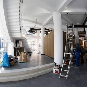 Część holu od strony korytarza. Po prawej stronie znajdują się tyły boksu kasowo-szatniowego. Po lewej widać spód schodów, które prowadzą na pierwsze piętro.