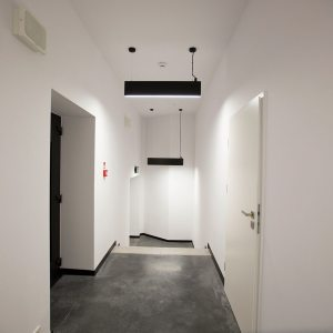 Wąski korytarz o białych ścianach i szarej podłodze. Z sufitu zwisają dwie czarne prostokątne lampy .