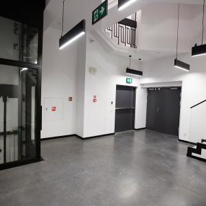 Szklana widna z czarnymi wykończeniami. Obok para czarnych drzwi i fragment schodów prowadzących na kolejne piętro.