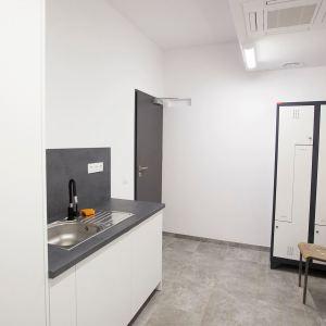 Niewielki pomieszczenie o białych ścianach i szarej podłodze. W rogu stoją podłużne białe szafki o czarnych krawędziach.