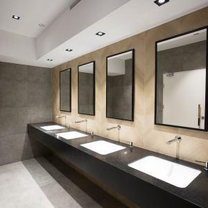 Toaleta. Nad każdą z czterech białych umywalek zamontowane lustro.
