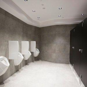Rząd białych pisuarów naprzeciwko rzędu czarnych kabin toaletowych