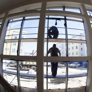 Dwóch pracowników na rusztowaniu przy oknach.