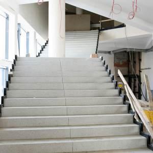 Białe schody o czarnym wykończeniu po bokach prowadzące na poziom pierwszy.