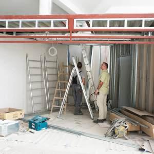Budowa boksu kasowo-szatniowego. Dwóch mężczyzn wewnątrz pomieszczenia stoi otoczonych drabinami.