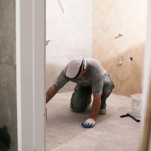 Pracownik gładzi posadzkę w toalecie.