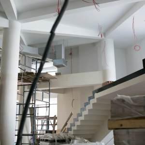 Hol główny. Z białego sufitu zwisają czerwone kable. Widać fragment schodów i rusztowanie.