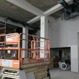 Na pierwszym planie pomarańczowy podnośnik.  Po lewej stronie rusztowanie. Po prawej we wnęce pracownik trzyma biały kabel.