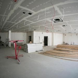 Przestronne pomieszczenie z dużymi oknami.  Z sufitu zwisają czerwone kable. Na podłodze leżą drewniane listwy i białe płyty.