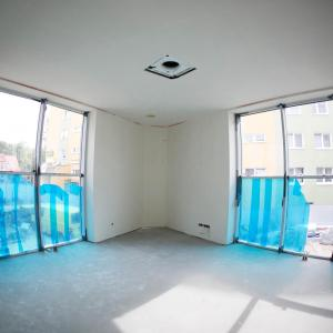 Gabinet dyrektora. Białe ściany. Wysokie okna do połowy zabezpieczone niebieską folią.