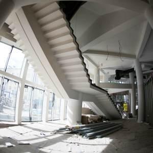 Spód schodów prowadzących na poziom pierwszy.  Po lewej stronie okna, po prawej boks kasowo-szatniowy.