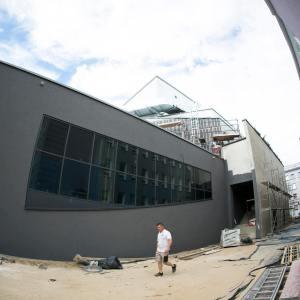 Boczna zewnętrzna ciemnoszara ściana budynku.  Ciemne okna. Pracownik w białej koszulce.