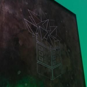 Jedna z prac - na brązoweym tle wykreslona wieża zakończona stożkami.
