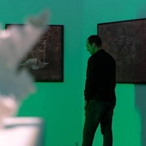 Odwrócony bokiem ubrany na ciemno mężczyzna ogląda wystawę. Ściany, na których wiszą prace oświetlone zielonym swiatłem.