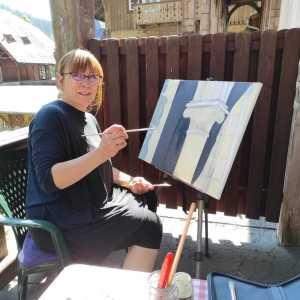 Kobieta z grzywką i w okularach siedzi na zielonym plastikowym krzesełku przed sztalugami.  W prawej ręce trzyma pędzel. Maluje na płótnie fragment kolumny.