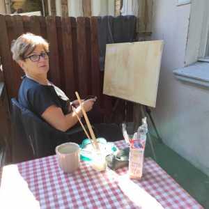 Krótko ścięta kobieta w okularach przed płótnem umieszczonym na sztaludze. Na stoliku na kraciastej ceracie kubek, talarzyk, paczka ciastek, etui i słoik z pędzlami.