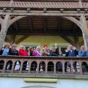 Uczestnicy pleneru na drewnianym balkonie pozują do zdjęcia. Zdjęcie robione z dołu.