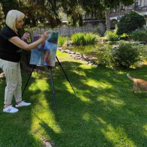 Kobieta z blond włosami z grzywką przy sztaludze rozstawionej na trawniku. W tle fragment budynku. Z prawej przemierzający trawnik rudy kot.