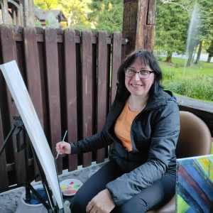 Uśmiechnięta kobieta na balkonie przy sztaludze. Za nią trawnik i tryskająca woda.