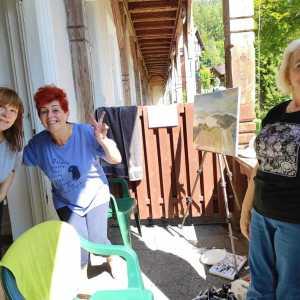 Trzy kobiety na balkonie. Jedna zagląda przez drzwi, druga demonstruje znak zwycięstwa, trzecia stoi przy balustradzie i opiera rękę o biodro. Cieszą się.