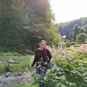 Iza Kostiukow na łonie przyrody. Potok, drzewa, po prawej kępa kwiatów.
