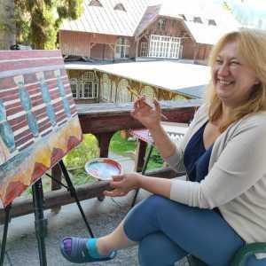 Roześmiana kobieta na plastikowym fotelu. W prawej ręce trzyma pędzel, w lewej tackę ro rozrabiania farb. Nogę założyła na nogę.Przed nią praca.