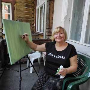 Uśmiechnięta kobieta pozuje do zdjęcia. Siedzii na plastikowym fotelu. W lewej ręce trzyma tubkę farb, w prawej pędzel, którym dotyka płótna. Za nią drewniana ściana budynku i okna. Po lewej balustrada balkonu.