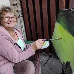 Uśmiechnięta kobieta pozuje przy swoim obrazie. Praca przedstawia pejzaż. W prawej ręce trzyma pędzel, w lewej tackę.
