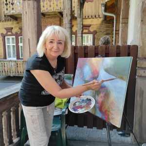 Kobieta na balkonie podczas malowania obrazu pozuje do zdjęcia. W tle fragment budynku w stylu tyrolskim.