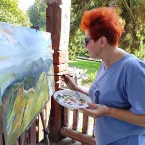 Rudowłosa kobieta maluje górski pejzaż.