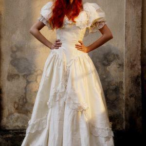 Rudowłosa kobieta w białej sukni ślubnej z bufiastymi rękawami.