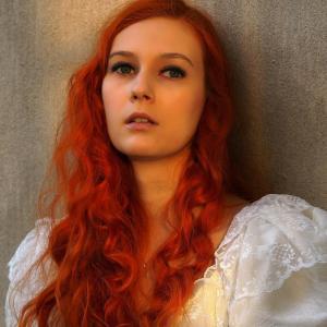 Portret rudowłosej młodej kobiety w białej sukni ślubnej. Spogląda ponad obiektyw. Ma lekko rozchylone usta.