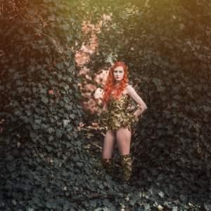 Rudowłosa młoda kobieta odziana skąpą suknią z imitacji zielonego bluszczu. Stoi wśród pnączy.