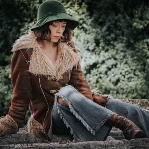 Szczupła brunetka w zielonym kapeluszu siedzi na kamieniu z podciągniętą do piersi prawą nogą. Ma na sobie beżową kurtkę. Jej mina wyraża smutek.