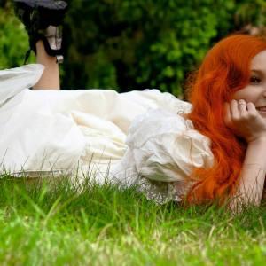 Rudowłosa młoda kobieta leży w trawie. Głowę podpiera na dłoniach.  Nogi ma zgięte w kolanach, czarne ciężkie buty na stopach.  Uśmiecha się.