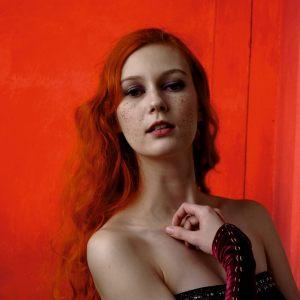 Rudowłosa młoda kobieta na tle czerwonej tkaniny. Ma gołe ramiona. Dłonią dotyka obojczyka. Spogląda w obiektyw.