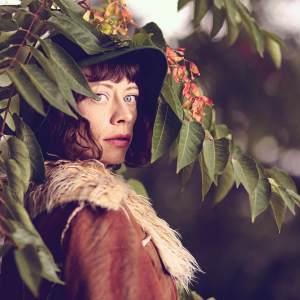 Brunetka w zielonym kapeluszu i beżowej kurtce stoi bokiem pod gałęzią. Podłużne zielone liście opadają na jej głowę.