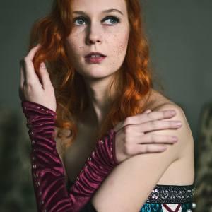 Rudowłosa szczupła kobieta. Ma niebieską suknię bez ramion i dekoltu., a także fioletowe rękawiczki sięgające od nadgarstka za łokcie.