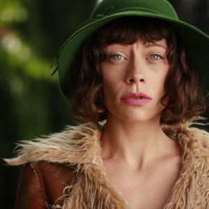 Brunetka w zielonym kapeluszu i beżowej kurtce odsłaniającej obojczyki spogląda w obiektyw.