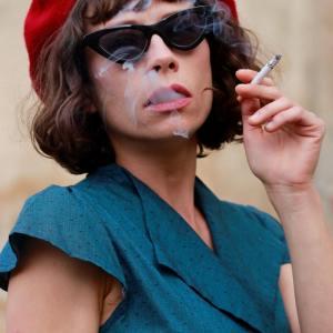 Brunetka w czerwonym berecie i niebieskiej letniej sukience. Ma duże ciemne okulary. Pali papierosa.