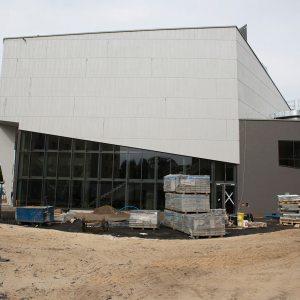Widok budynku z zewnątrz.  Boczna ściana jest w połowie szklana, a w połowie biała.