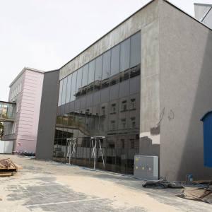 Widok budynku z zewnątrz. Ściana z ciemnego szkła. Obok niebieski kontener.