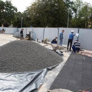 Pracownicy stoją przy blaszanym zewnętrznym ogrodzeniu placu budowy.