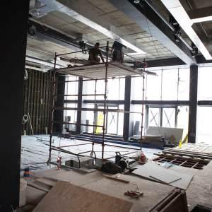 Remont w środku budynku. Przestronne pomieszczenie. Dwóch pracowników stoi na rusztowaniu.