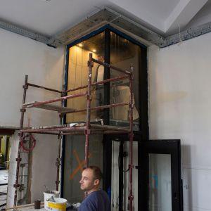 Przeszklona winda z czarnymi elementami. W środku pracownik.